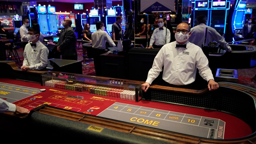 Dealers in masks wait for customers before the reopening of the D Las Vegas hotel and casino
