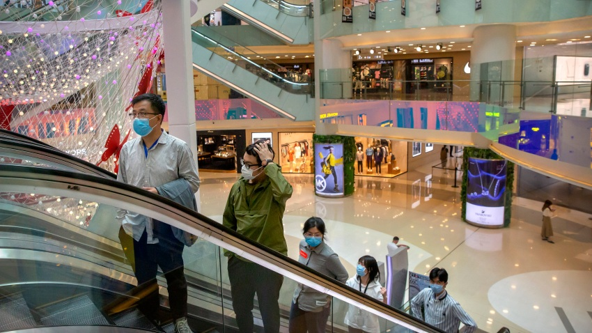 In this April 15, 2020 photo, people wear facemasks to protect against the spread of the new coronavirus cleans as they ride an escalator at a shopping mall in Beijing. China has reported its biggest economic decline since the 1970s as it fought the coronavirus in the first quarter of the year.