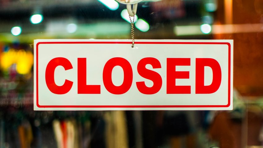 "A glass door with red and white ""closed"" store sign"