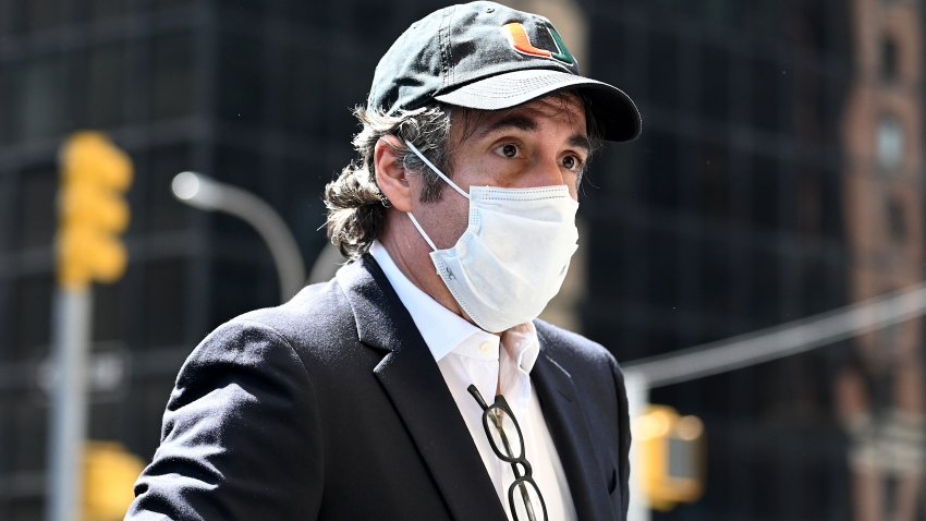 Michael Cohen returns home wearing mask.