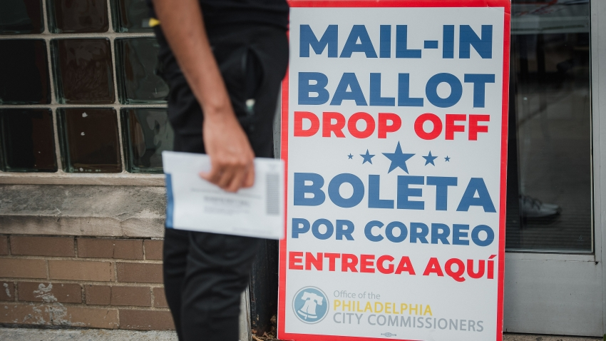 A voter waits to drop off a mail-in ballot.