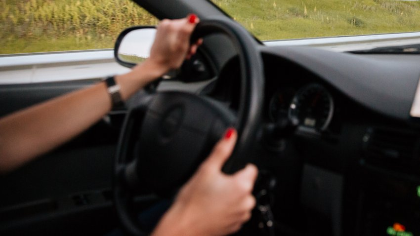 Woman driver driving car on the road