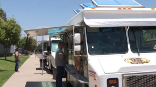 man stands at the window of a white food truck