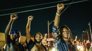 Protesters raise their fists during a demonstration against the shooting of Jacob Blake in Kenosha