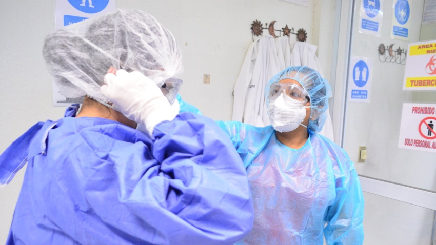 Dos enfermeras con equipo de proteccion personal.