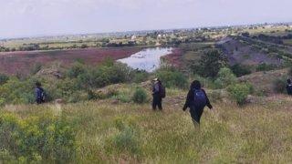 Tres personas buscan fosas clandestinas en un campo en México