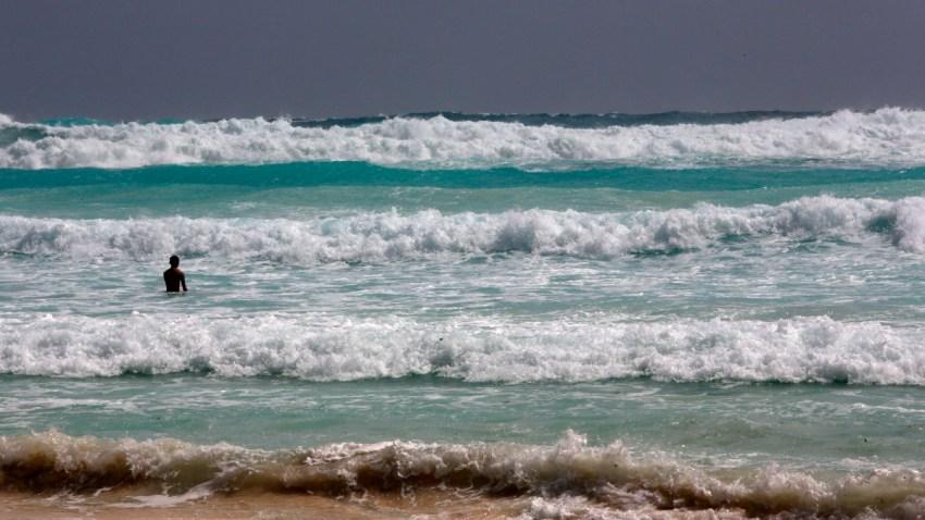 Bañista entre las olas de Cancún