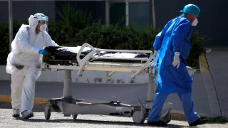 Personal médico traslada a fallecido por COVID