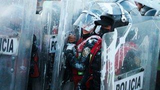 Policías entre escudos de protección
