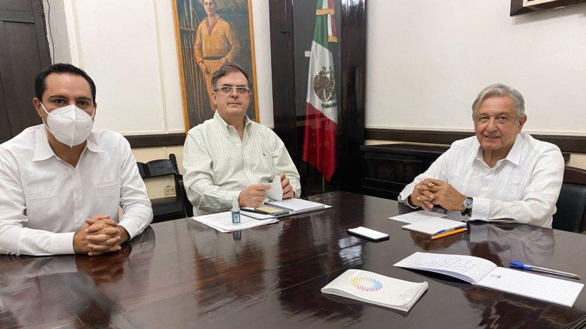 El presidente de México (d) con dos funcionarios sentados a una mesa