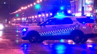 A Chicago police SUV blocks traffic on a rain-soaked street late Friday night after an officer-involved shooting