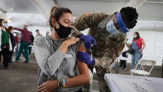 In this March 9, 2021, file photo, a U.S. Army soldier from the 2nd Armored Brigade Combat Team, 1st Infantry Division, immunizes Mariana Nascimento with the Pfizer COVID-19 vaccine at the Miami Dade College North Campus in North Miami, Florida.