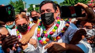 Polémico candidato mexicano luce collares de colores en un acto de campaña