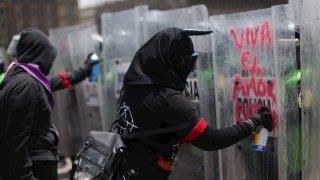 Mujeres vestidas de negro pintan un mensaje de amor en escudos policiales