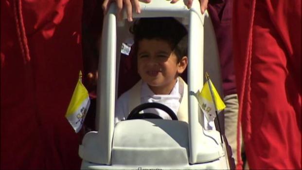 Niños recrean la caravana papal